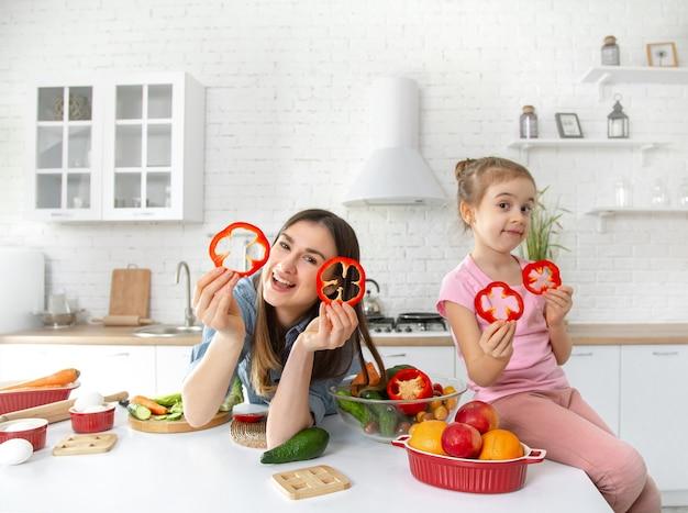 엄마와 딸이 부엌에서 샐러드를 준비합니다. 재미있게 야채를 가지고 놀아 라.