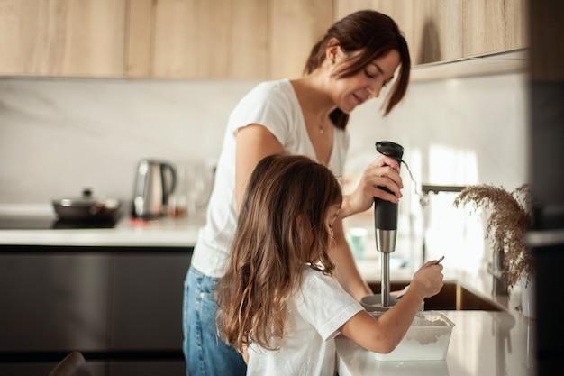 ママと娘は自宅のキッチンでジンジャーブレッドのアイシングを準備します。ブレンダーで叩きます。女の子
