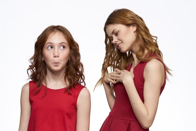 ママと娘の赤いドレスは家族の喜びの友情を抱きしめます