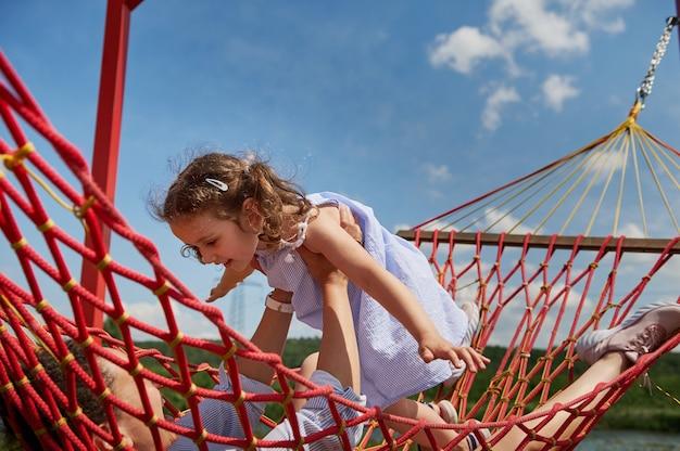 엄마와 딸은 해먹에서 쉬고 놀고 있습니다. 아기 소녀는 비행기 날개처럼 손을 벌렸습니다. 가족 관계 개념, 사랑, 애정, 부드러움.