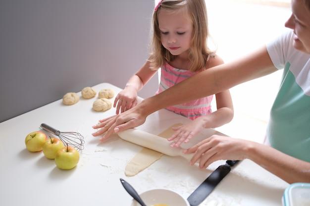 キッチンのテーブルで小麦粉生地を広げているママと娘。子育ての概念