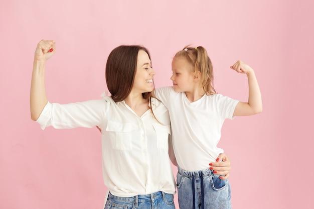 Мама и дочь демонстрируют свои мускулы и силу в студии на розовом фоне.