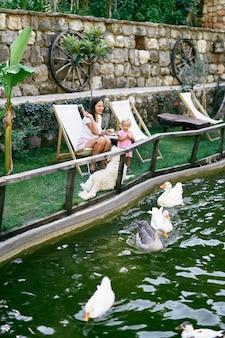 엄마와 딸은 잔디밭의 의자에 앉아 연못에서 오리에게 먹이를 준다