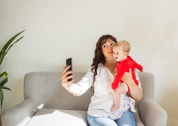 Мама и дочка сидят на диване и фотографируются