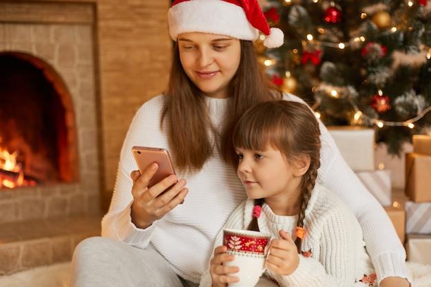 クリスマスツリーの近くに座って、抱き締めて、ビデオ通話でコミュニケーションを取り、楽しんでいるママと娘。