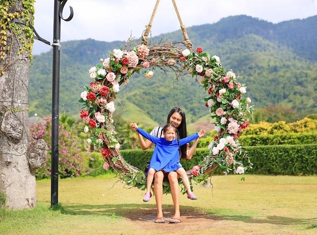 母と娘は自然の庭にカラフルなバラの花とバスケットスイングに座って