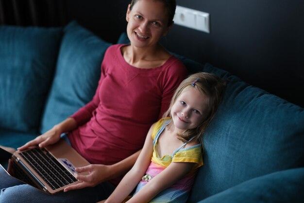 Мама и дочь сидят на диване с ноутбуком и кредитной банковской картой
