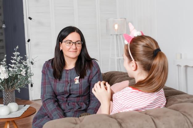 Мама и дочь сидят на диване и болтают. девушка-подросток с эмоциями рассказывает историю матери