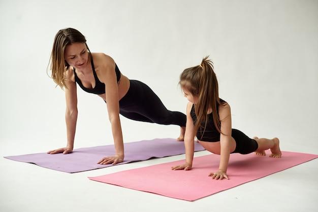 엄마와 딸이 아침 요가 연습을합니다.