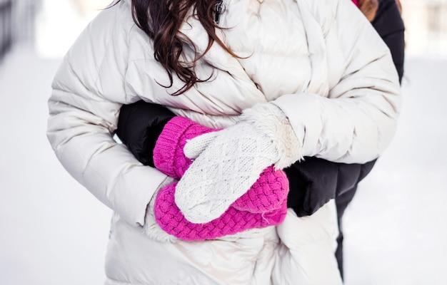 Мама и дочь вместе проводят время на свежем воздухе зимой. мама обнимает дочь. яркие перчатки крупным планом. фото