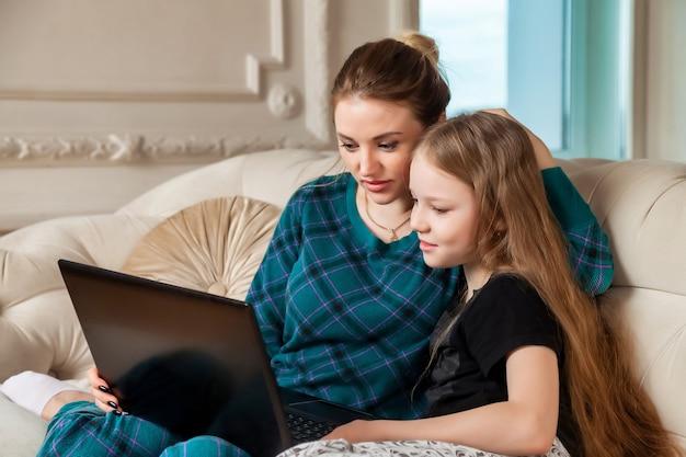 Мама и дочь проводят время вместе с ноутбуком дома в гостиной на диване. счастливые кавказские мама и дочь с помощью компьютера смеются, просматривают интернет, делают покупки в интернете, смотрят фильм