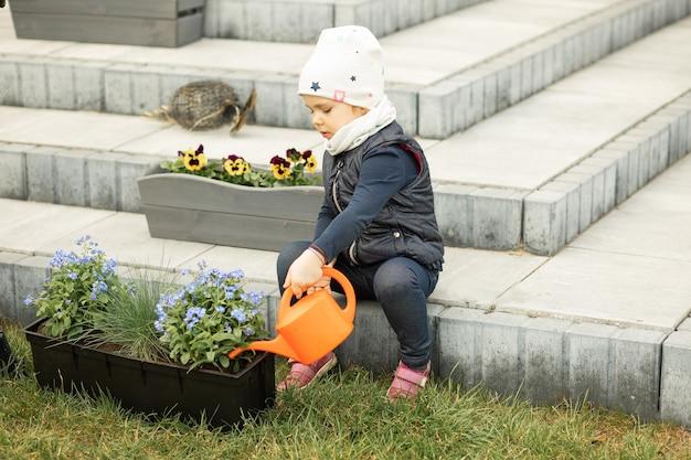 엄마와 딸이 집 앞마당이나 뒷마당에서 함께 시간을 보내고, 꽃을 심고, 물 뿌리개로 물망초에 물을주는 소녀, 아이들을 숙제에 끌어 들이기
