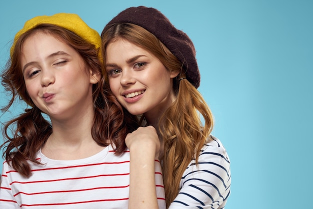 ママと娘のストライプのtシャツは楽しいライフスタイルの青い背景を抱きしめます。高品質の写真