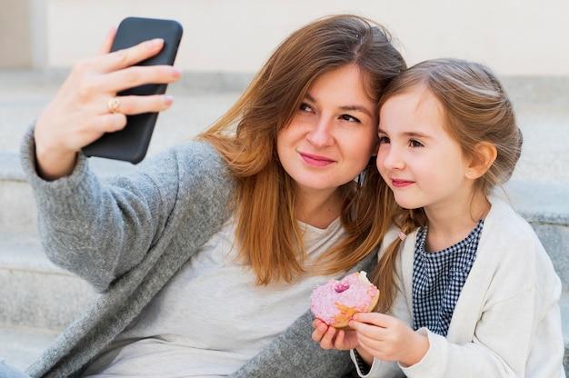 Мама и дочь, принимая селфи