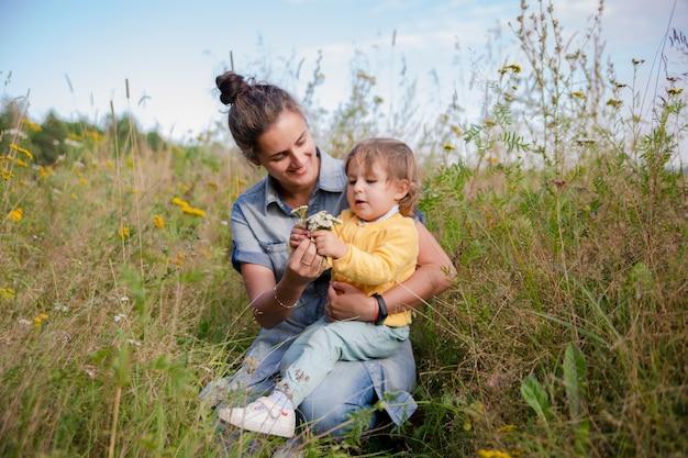 ママと娘の幼児は野花の花の花束を収集しますノコギリソウのクローズアップ