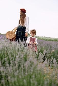 엄마와 딸은 함께 바구니에 라벤더 꽃을 모읍니다.