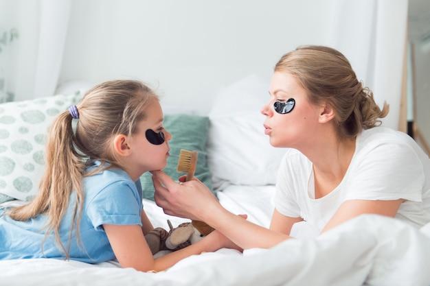 Мама и дочь используют патчи для глаз и щетку для ухода за кожей лица спа и процесс ухода за телом