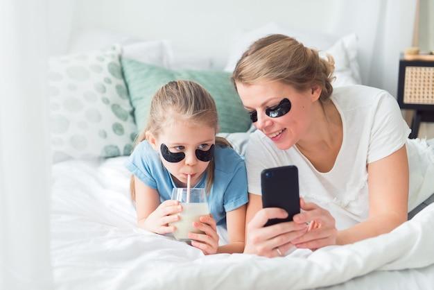 Мама и дочь используют повязки для глаз, пьют смузи и делают селфи или делают видеозвонки в спа-салоне и процедурах по уходу за телом
