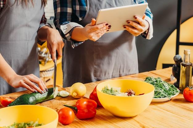 Мама и дочь с помощью планшета при приготовлении пищи на кухне
