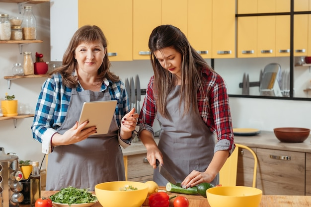 엄마와 딸이 주방에서 요리 할 때 태블릿을 사용하여