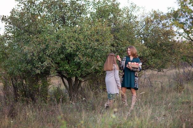 ママと娘は牧草地を歩く