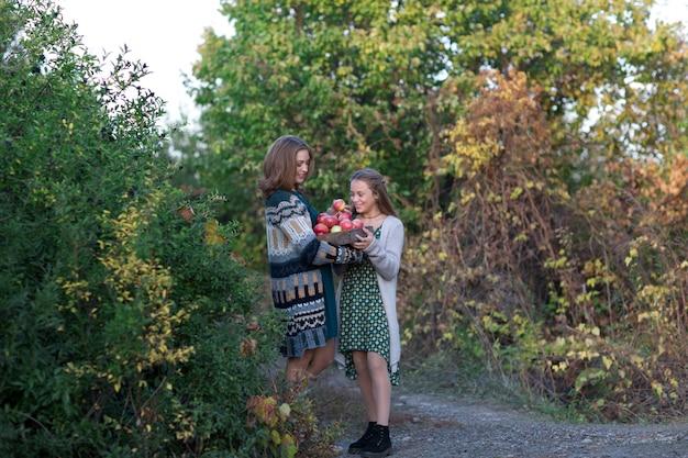 ママと娘が摘みりんごの上を歩く