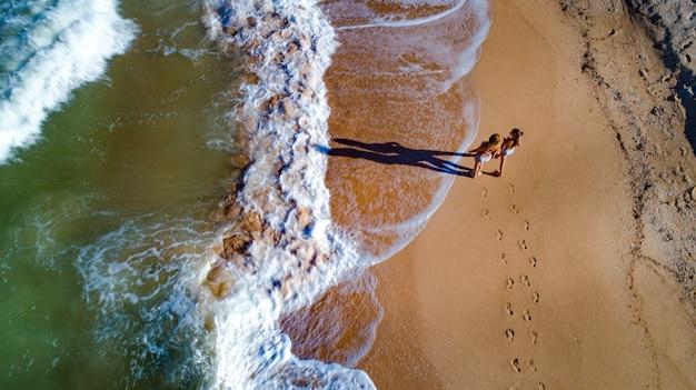 ママと娘が海岸沿いの波を歩く
