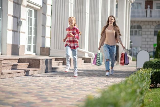 ショッピングバッグを持って通りを歩いているママと娘