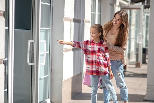 Мама и дочь гуляют по улице с сумками для покупок