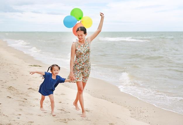 母親の手でカラフルな風船でビーチで歩く母と娘