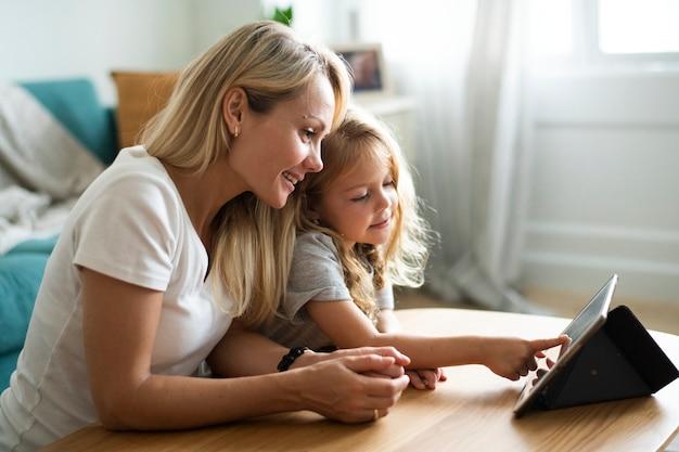 Мама и дочь смотрят мультфильм на цифровом планшете