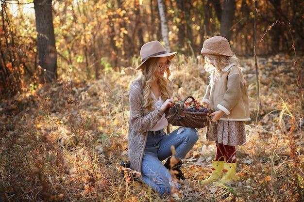 秋のベリーのバスケットを持つママと娘