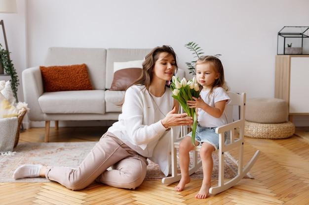 家で春のチューリップの花束を持つママと娘