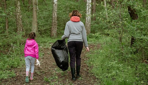 Мама и дочь мешками для мусора очищают окружающую среду от мусора.