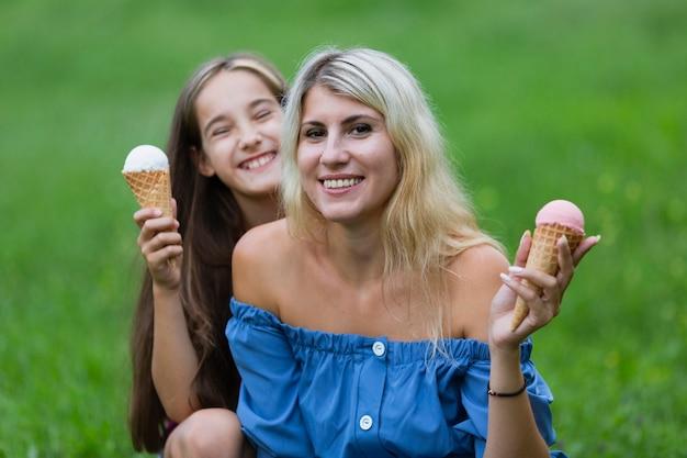 Мама и дочка с мороженым в парке