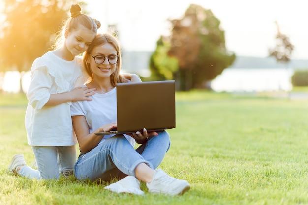 Мама и дочь с ноутбуком, отдыхая на лугу