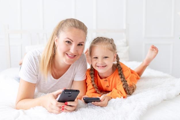 携帯電話を持ったママと娘が自宅のベッドに横になって、自分撮りをしたり、ビデオリンクを介して話している