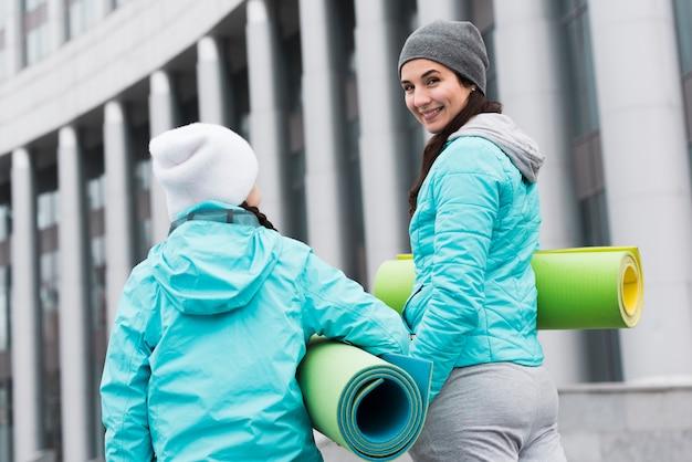 Мама и дочка с ковриком для йоги