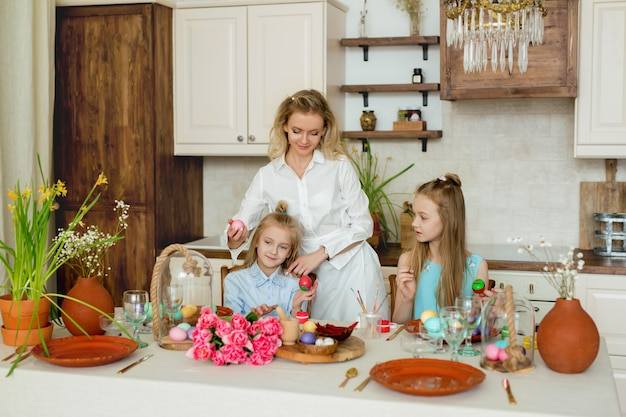 엄마와 딸은 부엌에서 부활절 달걀 그림에 종사하고 있습니다.