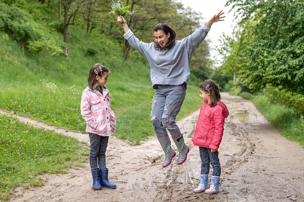 春のゴム長靴で雨が降った後、ママと娘が森を歩いています