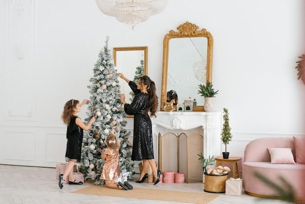 새해 축하를 위해 크리스마스 트리를 장식하는 엄마와 딸들