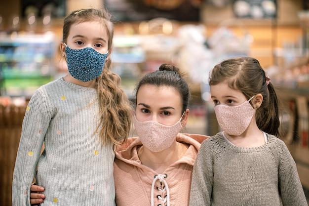コロナウイルスのパンデミックのクローズアップのため、検疫中にママと娘が店でマスクを使って買い物をします。