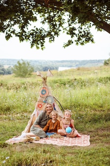 엄마와 딸이 여름에 야외에서 시간을 보내고 wigwam 장식 옆에 앉아 있습니다.
