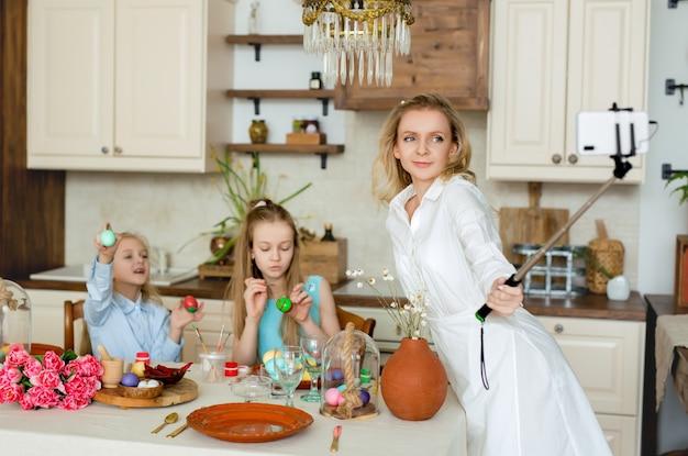 ママと娘はお祝いのイースターテーブルのキッチンで自分撮りをします