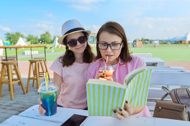 ママと娘のティーンエイジャーは楽しい本を見て、読んで楽しんでいます。