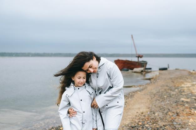 ママと娘は湖の近くのボートの背景に楽しい時を過す