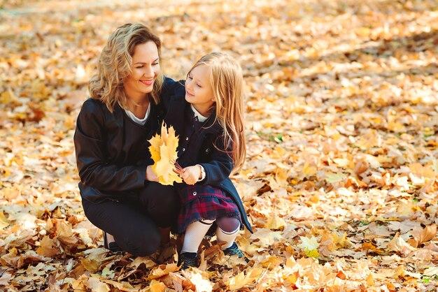 Мама и девочка вместе весело проводят время на открытом воздухе осенью.