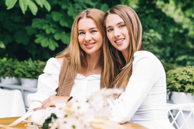 ママと女の子の笑顔とカフェの夏のテラスで抱き締める