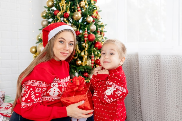 빨간 스웨터와 모자를 쓴 엄마와 그녀의 아기 아들은 집에서 크리스마스 트리 아래에서 선물을 주고 새해와 크리스마스를 기뻐합니다