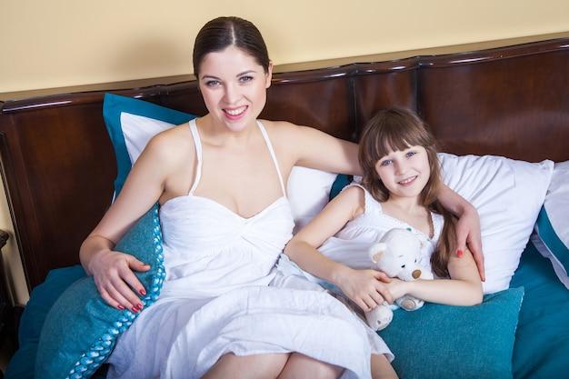 Мама и ее красивая девушка лежат в постели по утрам, обнимаются, зубасто улыбаются и смотрят в камеру. студийный снимок